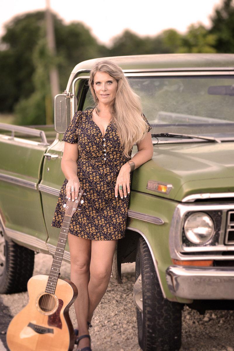 Ashley Davis w guitar and truck